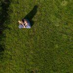Drohnenaufnahme einer jungen Frau mit Hut auf einer grünen Wiese