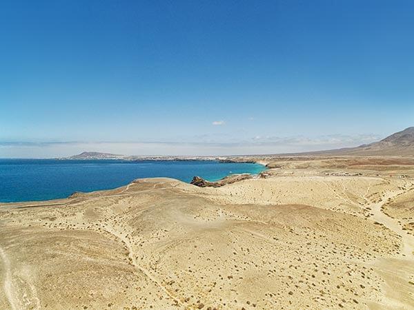 Cremig weißer Sandstrand am Wasser unter strahlend blauem Himmel von oben