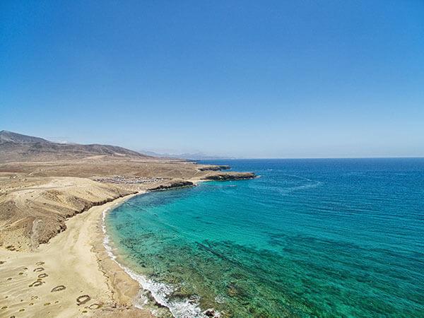 Türkis blaues Meer am Sandstrand der Kanaren aus der Luft