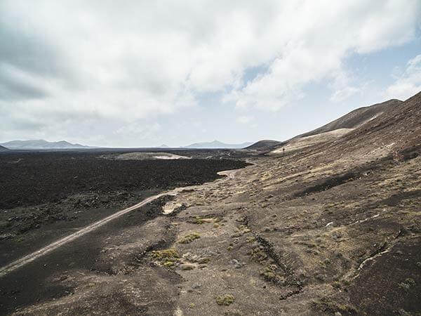Landstraße führt durch kanarisches Gebirge unter einer weißen Wolkendecke