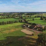 Bauernhöfe umgeben von sonnigen gelben und grünen Feldern
