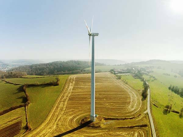 Windrad von oben mit Aussicht auf grüne Felder und Berge