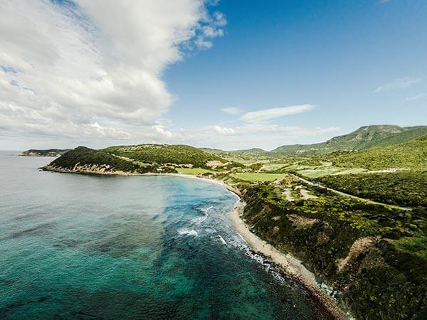 Strandbucht an grünen Bergen unter blauem Himmel