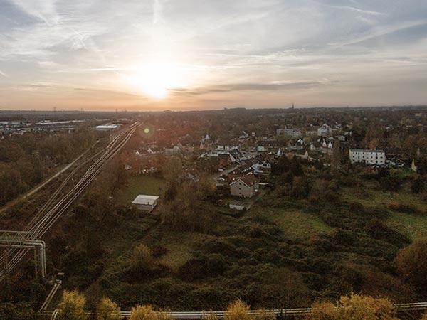 Immobilien und Bahngleise bei Sonnenuntergang aus der Luft