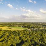 Luftaufnahme einer Landschaft umgeben von einer Waldfläche